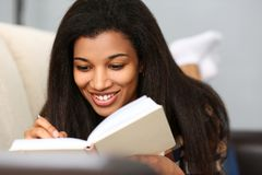 Smiling black woman write story in notebook stock image