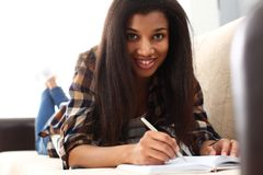 Smiling black woman write story in notebook stock photo