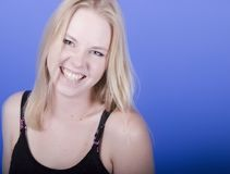 Smiling Blond. A smiling blond against blue background Royalty Free Stock Image