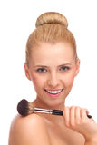 Smiling blond beauty touching shoulder with make-up brush. Royalty Free Stock Images