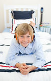 Smiling blond boy listening to music Stock Photography