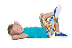 Smiling blond boy rests on the floor Stock Photos