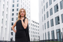 Smiling blond business woman with red lipstick on urban background Royalty Free Stock Photography