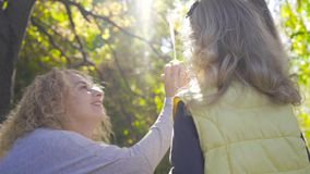 Smiling blond caucasian woman with curly hair sitting in the sunrays and playing soap bubbles with her little pretty. Daughters. Family with two kids having fun stock footage