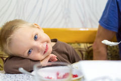 Smiling blond child when feeding Stock Photo