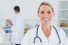 Smiling blond doctor posing with doctor attending patient on bac Stock Image