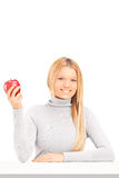 A smiling blond female holding a red apple on a table Stock Images