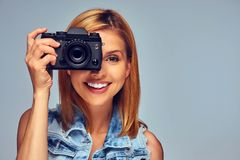 Smiling blond female holds compact digital photo camera. Stock Photos