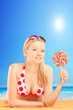 Smiling blond female lying on a towel and holding a lollipop, on Stock Photography