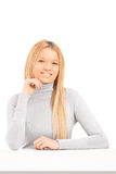 A smiling blond female posing on a table Stock Photography