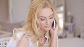 Smiling Blond Female Talking through Phone. Close up Smiling Young Female Talking through Phone While Touching her Blond Hair stock video footage