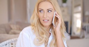Smiling Blond Female Talking through Phone Royalty Free Stock Photos