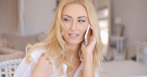 Smiling Blond Female Talking through Phone Stock Photography