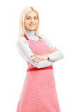 Smiling blond female wearing an apron and looking at camera Stock Image