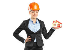 Smiling blond forewoman holding a model house Stock Photo