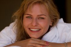 Smiling blond girl in bathrobe Royalty Free Stock Image