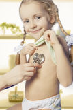 Smiling blond girl is being treated by doctor Royalty Free Stock Images