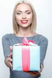 Smiling blond girl giving present Royalty Free Stock Photo
