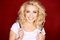 Smiling blond girl holding cosmetic brushes Stock Photography