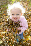 Smiling blond girl holding handful of autumn leaves Stock Images