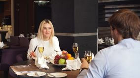Smiling blond girl is listening to her boyfriend. During the date, pleasant weekend, young people resting at the cafe stock video