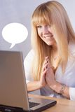 Smiling blond girl makes videochat online with laptop computer Royalty Free Stock Photography