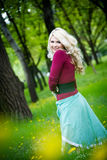 Smiling blond girl over green grass Royalty Free Stock Photos