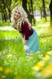 Smiling blond girl over green grass Royalty Free Stock Images