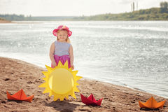 Smiling blond girl posing with paper boats Stock Photography