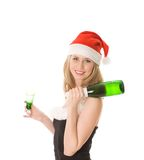 Smiling blond girl in santa hat holding bottle Royalty Free Stock Photo
