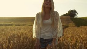 Smiling blond girl wonders cross the field of wheat, woman of fashion, the sun is shining. Slow motion, stabilizer shots. Smiling blond girl wonders cross the stock video footage