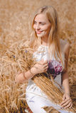 Smiling blond lady with sheaf of wheat sticks Stock Photos