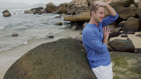 A smiling blond man in a blue shirt is standing on the beach near large stones and straightening his hair stock video footage
