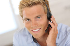 Smiling blond man talking on headset. Smiling attractive customer service representative Stock Photography