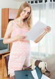 Smiling blond pregnant woman with documents in home interior Stock Photo