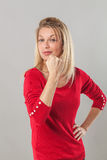 Smiling blond 20s woman with fist tight, foreground Royalty Free Stock Images