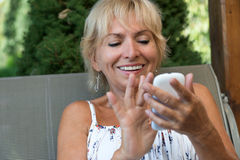 Smiling blond senior woman is controlling her smartphone Royalty Free Stock Photography
