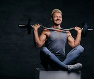 Smiling blond sporty male sits on a white box with crossed legs and holds barbell. royalty free stock photo