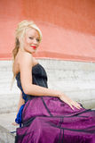 Smiling blond woman. Portrait of smiling blond woman in purple dress posing outdoors Stock Photo