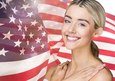 Smiling blond woman against american flag Stock Photo