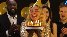 Smiling blond woman in birthday hat blowing candles on cake, friends applauding. Stock footage stock video footage