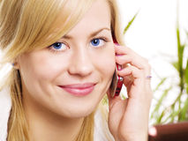 Smiling blond woman calling by phone Royalty Free Stock Photography