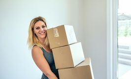 Woman carrying moving boxes. Smiling blond woman carrying three moving boxes Royalty Free Stock Image