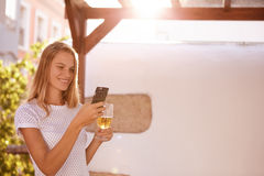 Smiling blond woman with cellphone and beer Royalty Free Stock Image