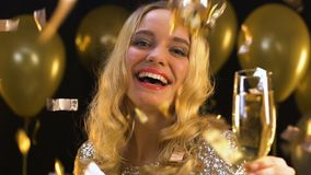 Smiling blond woman with champagne glass standing under falling confetti, party. Stock footage stock video
