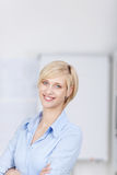 Smiling blond woman with crossed arms Royalty Free Stock Photos