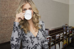 Smiling Blond Woman Drinking Coffee In Office Royalty Free Stock Images