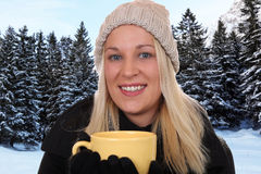 Smiling blond woman drinking cup of tea outdoor in winter Stock Images