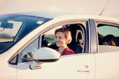 Smiling blond woman driving a car Royalty Free Stock Photos