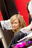 Smiling blond woman drying her hair. In a hairdressing salon Royalty Free Stock Image